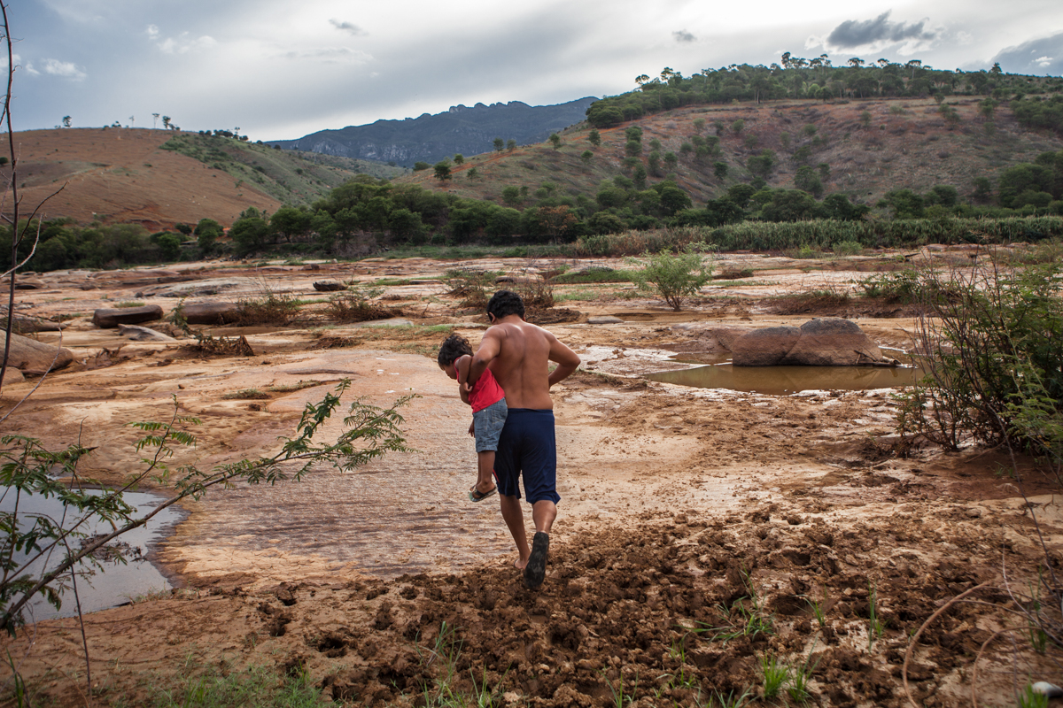 December 2015, indigenous reserve Krenak in Resplendor: Rondon, the most respected leader of the clan, raises his child from the ground to avoid touching the toxic mud